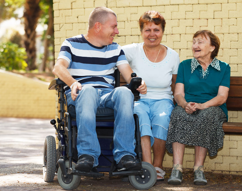 Two ladies sitting beside a man in wheelchair.
