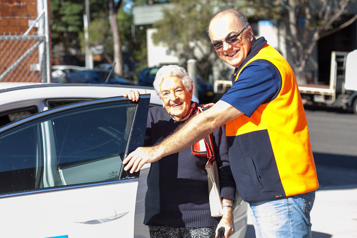 Easylink driver helping older woman into car.