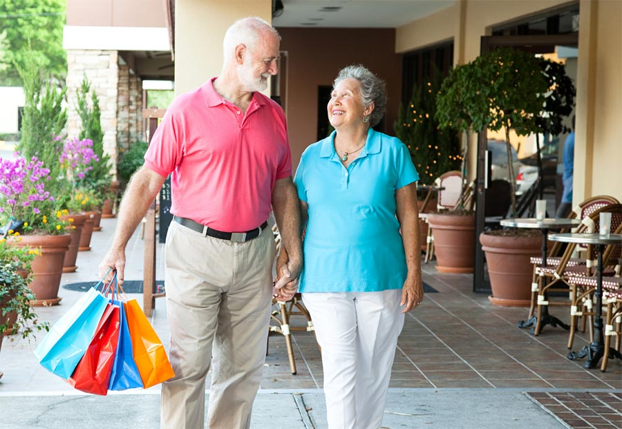 Older man with shopping bags and older woman holding hands, walking through shopping centre.