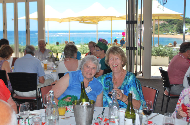 Two smiling ladies, seated at a restaurant with views of the beach in the background.