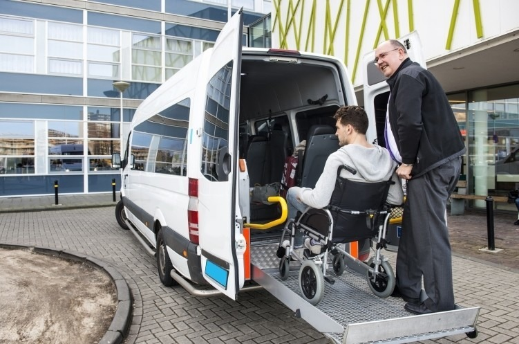 Man assisting a young man in a wheelchair out of an accessible bus.