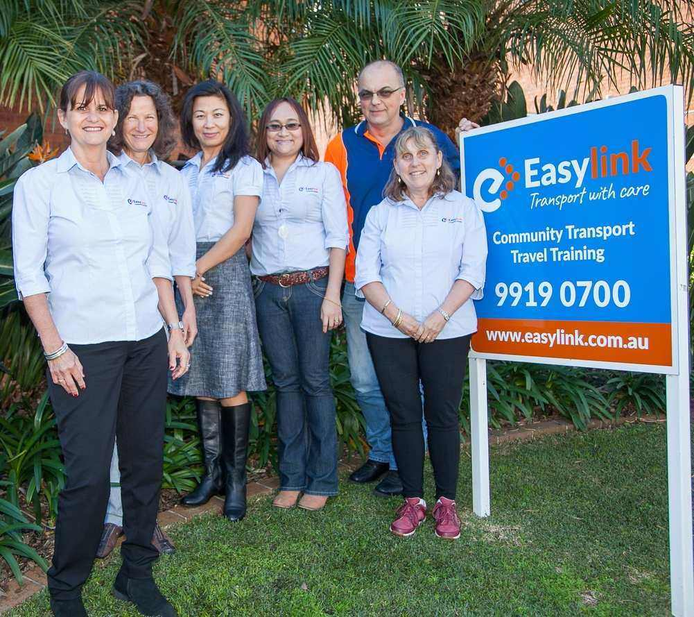 Easylink staff standing beside Easylink signboard.